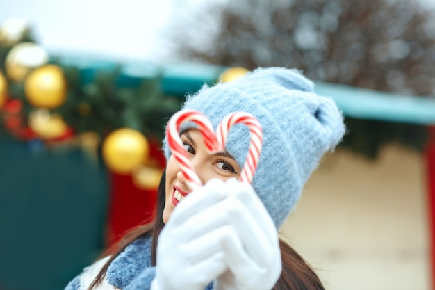 ハートの形でキャンディーを保持している幸せなブルネットの女性
