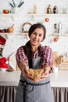 Счастливая брюнетка женщина держит тесто в форме сердца на кухне