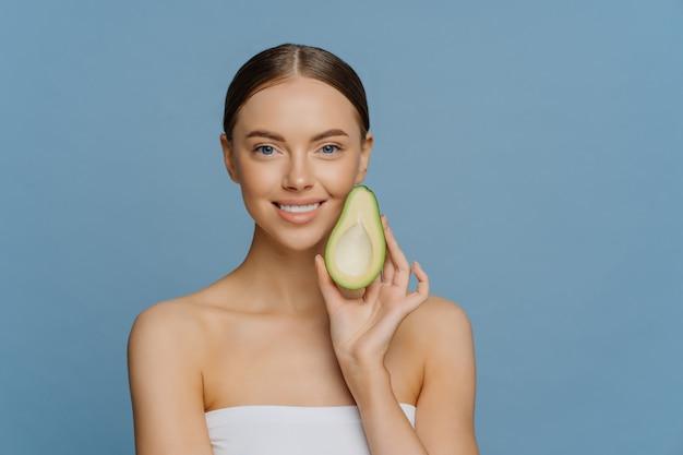 Happy brunette woman holds half of avocado near face