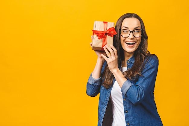 ギフトボックスを保持しているカジュアルな幸せなブルネットの女性