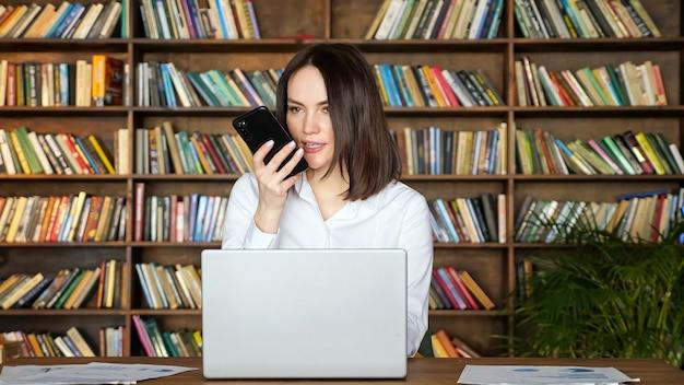세련된 흰색 블라우스를 입은 행복한 브루네트 여성은 방에 있는 큰 책장에 기대어 테이블에 있는 현대적인 노트북 근처에서 휴대폰으로 이야기합니다.