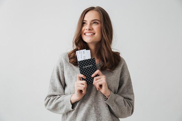 Счастливая брюнетка в свитере готовится к поездке, держа паспорт с билетами и глядя на серую стену