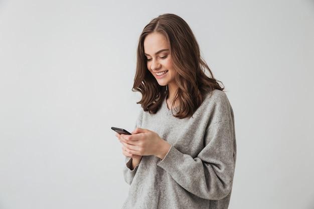 Счастливая брюнетка женщина в свитере писать сообщение на смартфоне над серой стеной