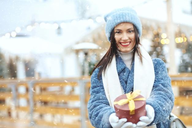降雪時のクリスマスフェアでギフトボックスを保持している冬のコートで幸せなブルネットの女性。テキスト用のスペース