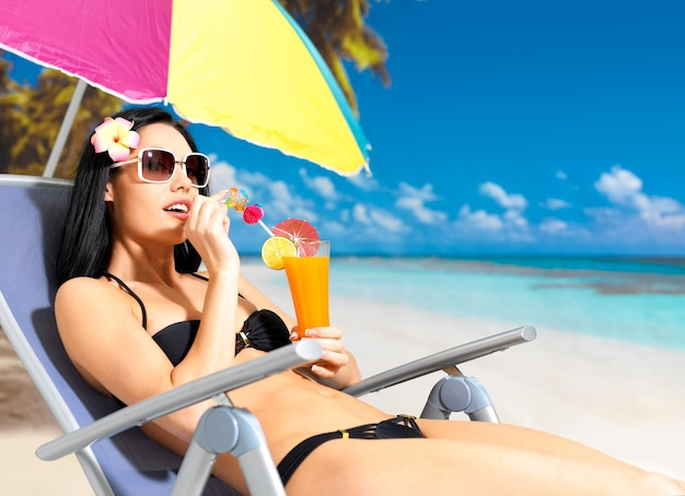 휴가 해변에서 오렌지 주스를 마시는 행복 한 갈색 머리 여자