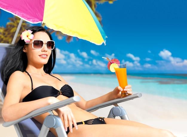 ビーチで楽しんで休暇中の幸せなブルネットの女性