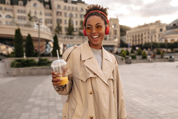Happy brunette woman in oversized beige trench coat listens to music in red headphones, smiles, holds orange juice glass outside