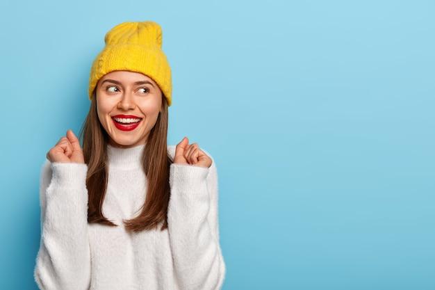 幸せなブルネットの女性は、くいしばられた握りこぶしを上げ、前向きに笑い、脇を見て、機嫌が良く、大学での試験に合格したことを祝う屋内で緩い白いセーターのポーズを着ています
