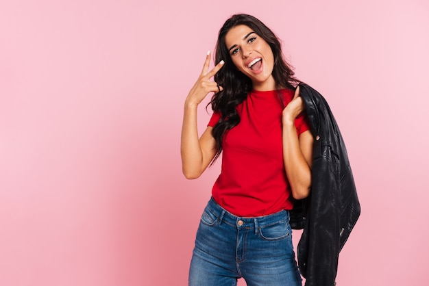 Happy brunette woman showing peace sign and looking at the camera while holding jacket on her shoulder over pink