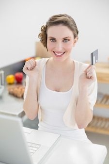 Happy brunette woman sitting in kitchen while home shopping