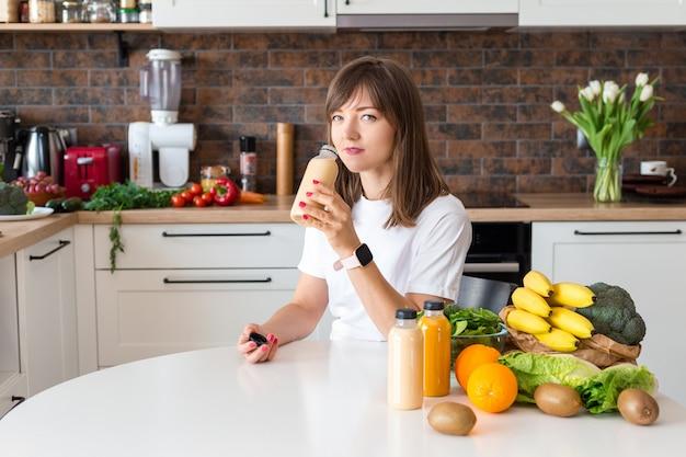 집 부엌에서 스무디 한 병과 과일을 들고 앉아 있는 행복한 브루네트 여성. 채식주의 식단과 해독 개념. 신선한 칵테일을 마시는 흰색 티셔츠와 소녀입니다. 포장 모형