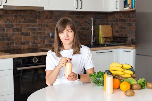 집 부엌에서 스무디 한 병과 과일을 들고 앉아 있는 행복한 브루네트 여성. 채식주의 식단과 해독 개념. 신선한 칵테일을 여는 흰색 티셔츠를 입은 소녀. 조롱