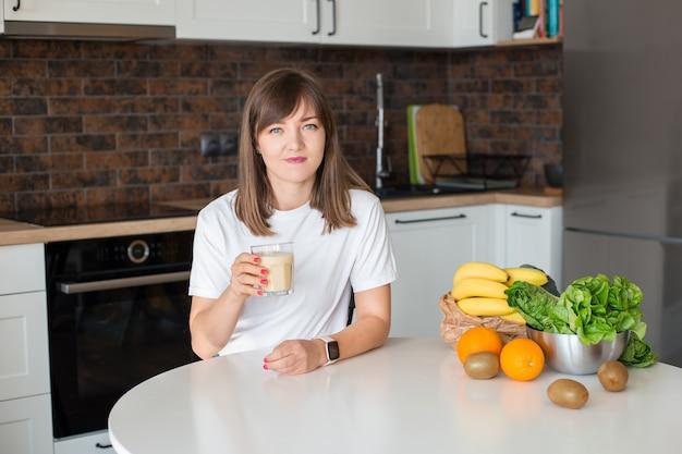 自家製のガラスのスムージーと家庭の台所で健康的な果物と一緒に座っている幸せなブルネットの女性。ビーガンミールとデトックスのコンセプト。新鮮なカクテルを飲む白いtシャツの女の子