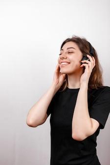 Счастливая брюнетка женщина улыбается, слушать музыку в наушниках на белом фоне, изолированные