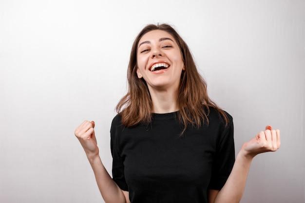 Счастливая женщина брюнет усмехаясь пока смотрящ камеру на изолированном пустом пространстве