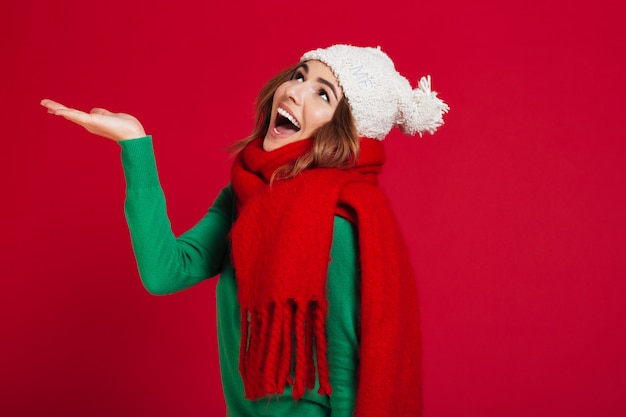 Happy brunette woman in sweater, funny hat and scarf