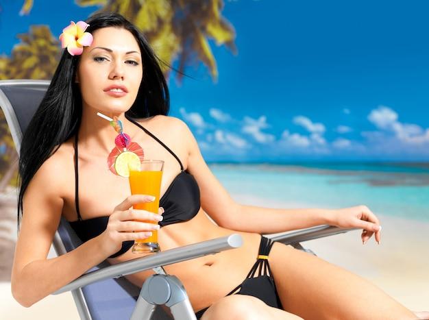 Felice donna bruna in vacanza godendo in spiaggia