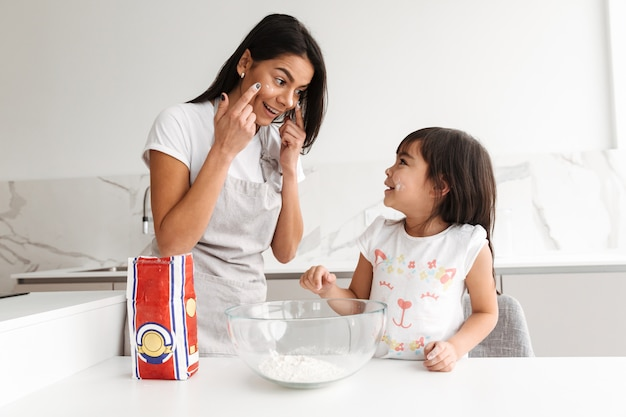 Happy brunette woman wearing apron cooking with her little daughter together in kitchen at home, putting flour on face for fun