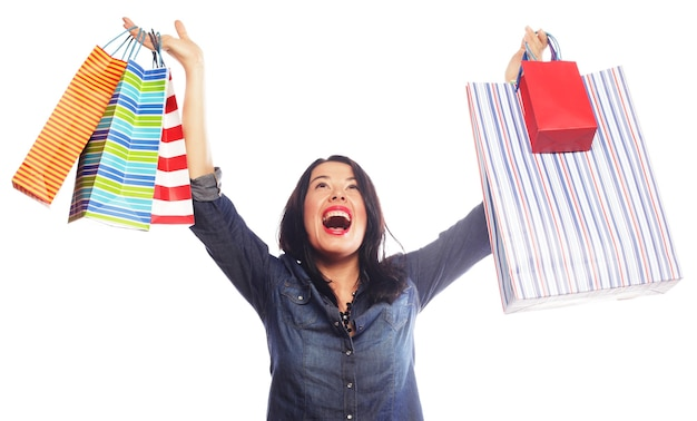 Happy brunette woman with shopping bags over white background