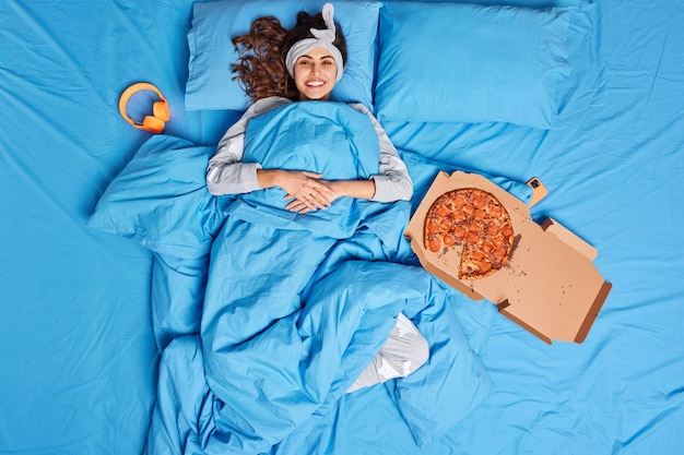 Happy brunette young woman enjoys lazy day in comfortable bed wears headband lying under soft blanket eats tasty pizza