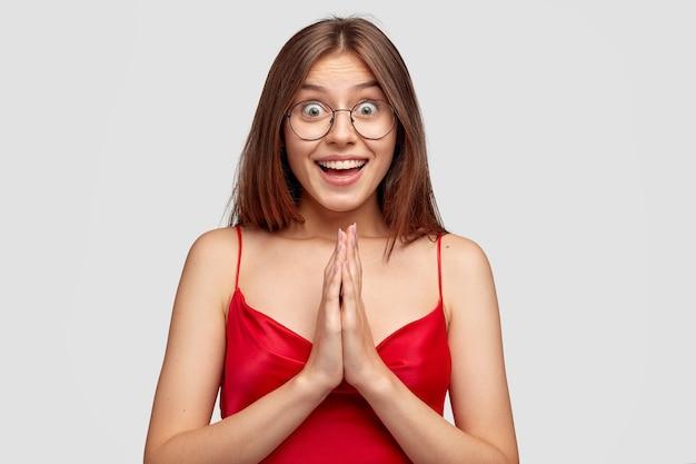 白い壁に対してポーズをとって幸せなブルネットの若い女性