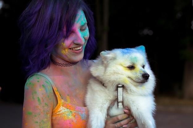小さな白い犬と幸せなブルネットの若い女性は、カラフルなホーリーパウダーをカバー