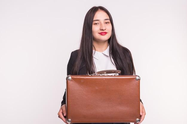 白地にレトロなスーツケースを保持している赤い唇を持つ幸せなブルネットの若い女性。