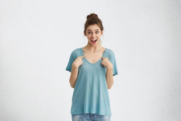 自分を指して興奮して口を開けている青い特大tシャツのハッピーバグアイラッキー女性