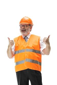 Il costruttore felice in un giubbotto di costruzione e un casco arancione che sorride allo studio