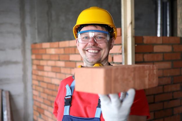 Счастливый строитель держит кирпич для кладки и улыбается.