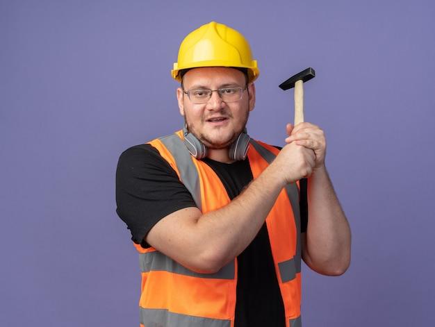 Felice uomo costruttore in giubbotto da costruzione e casco di sicurezza che tiene martello guardando la telecamera sorridendo allegramente in piedi sopra il blu