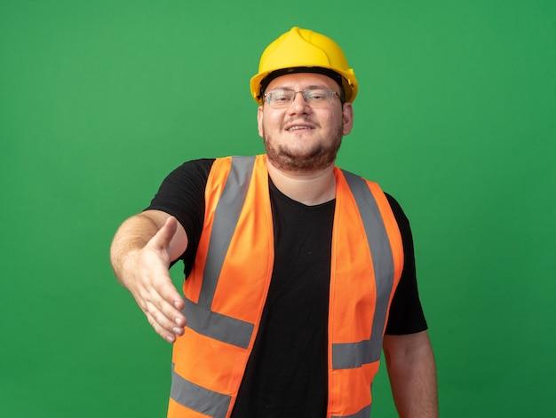Felice uomo costruttore in giubbotto da costruzione e casco di sicurezza che offre gesto di saluto con la mano sorridente amichevole in piedi su sfondo verde