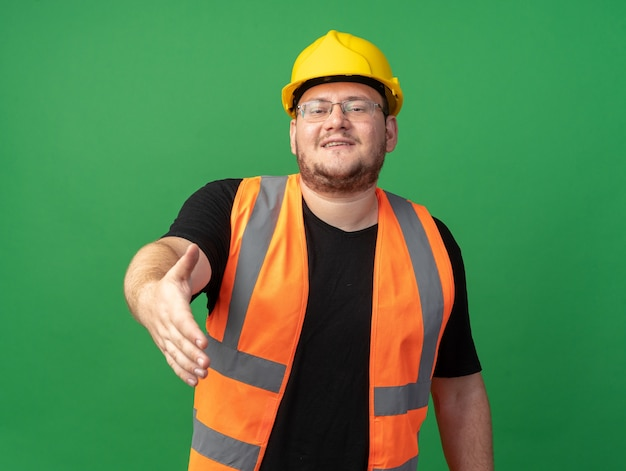 건설 조끼와 안전 헬멧을 쓴 행복한 빌더 남자는 녹색 배경 위에 친절한 미소를 지으며 손으로 인사하는 제스처를 제공합니다.