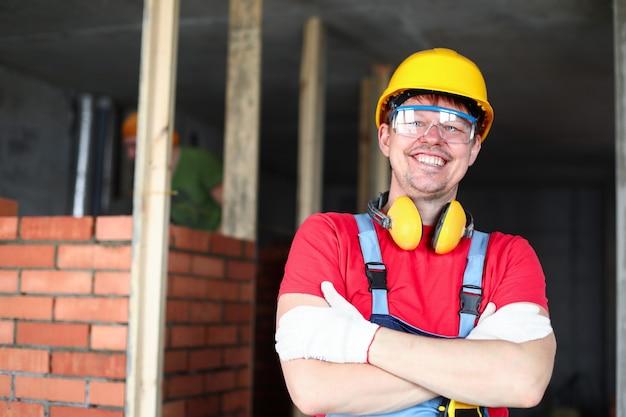 Счастливый строитель стоит возле кирпичной кладки и улыбается. оперативность строительного персонала, настроение и комфорт на объекте. строитель в каске скрестил руки на груди. перепланировка и зонирование