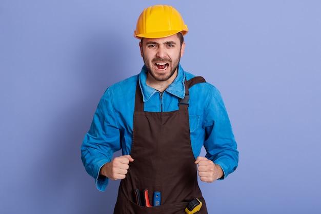 Happy builder wearing construction yellow helmet