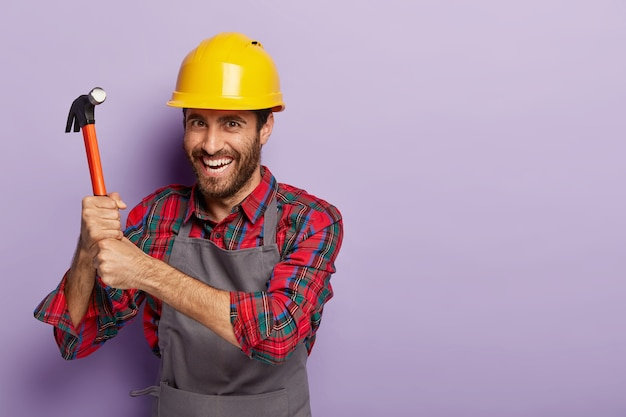 Happy builder wears construction helmet, does repairing with hammer