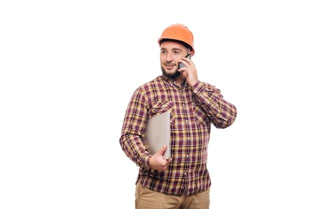 ラップトップを保持し、白い背景で隔離の電話で話している保護構造のオレンジ色のヘルメットの幸せなビルダー労働者。テキスト用のスペースをコピーします。働く時間。