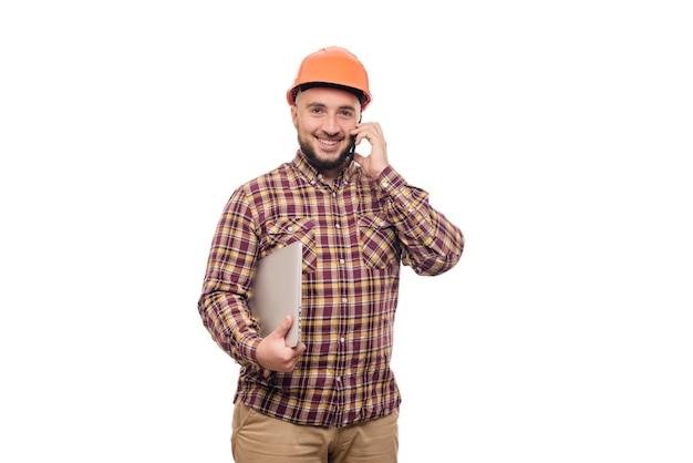 Счастливый рабочий строитель в защитном строительном оранжевом шлеме, держащем компьтер-книжку и говорящем по телефону, изолированному на белой предпосылке. скопируйте место для текста. время работать.