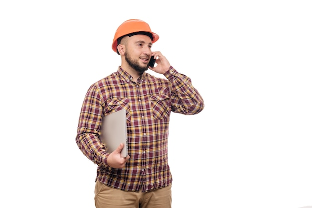 Happy builder worker in protective construction orange helmet holding a laptop and talking on the phone, isolated on white background. copy space for text. time to work. Premium Photo