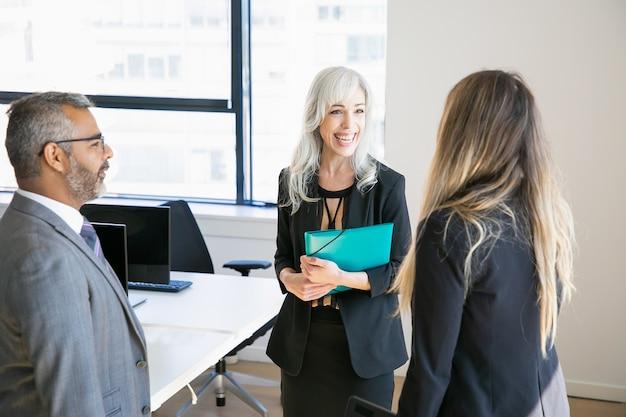 スーツを着て、オフィスに立って、話したり笑ったりして幸せなビジネス仲間。ミディアムショット。同僚のコンセプト