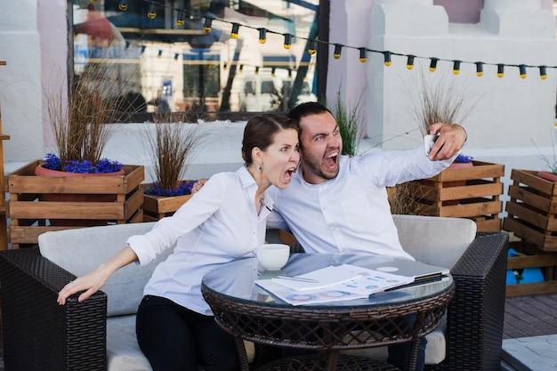 屋外レストランで幸せなビジネスカップル撮影selfie