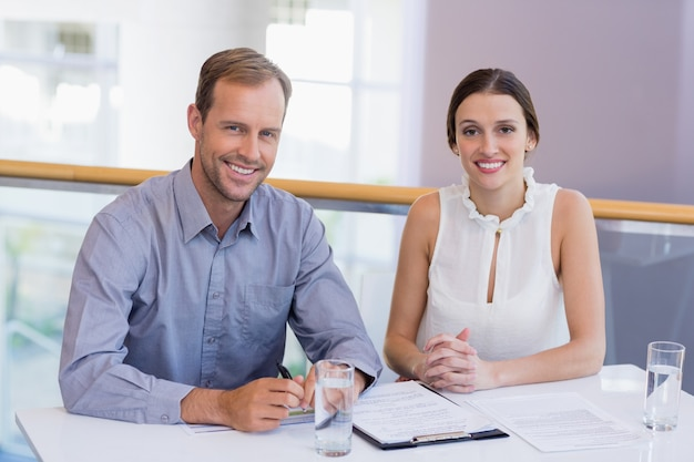 Happy business executives sitting at desk