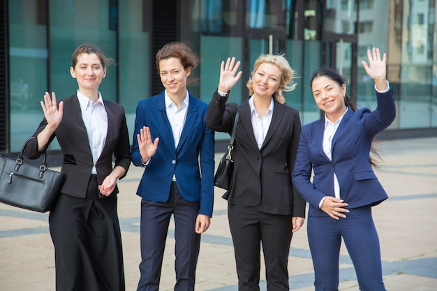幸せなビジネスレディースチームは、こんにちは手を振って、事務所ビルの近くに一緒に立って、カメラ目線と笑顔します。ミディアムショット、フロントビュー。ビジネスウーマングループの肖像画のコンセプト