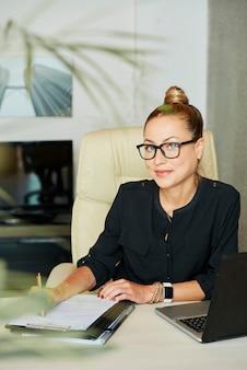 Счастливая бизнес-леди за столом в офисе