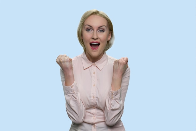 Happy business lady is showing yes gesture. joyful european businesswoman isolated on blue background.