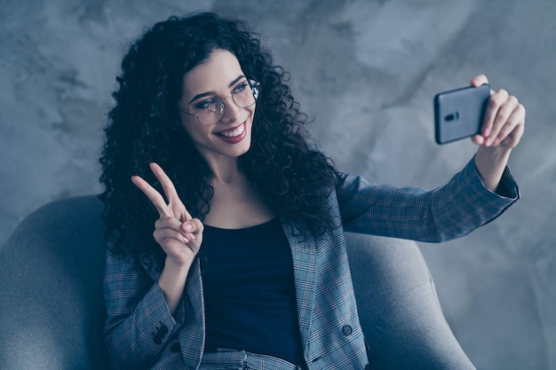 Happy business lady sit in chair making selfie showing v-sign isolated over concrete wall