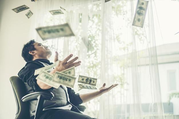Счастливый деловой человек заработал долларовые купюры нам деньги под денежным дождем