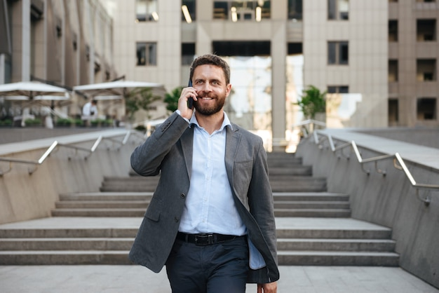 モダンなビジネスセンターの外の階段を降りながら携帯電話で話す灰色のスーツで幸せなビジネスの男性