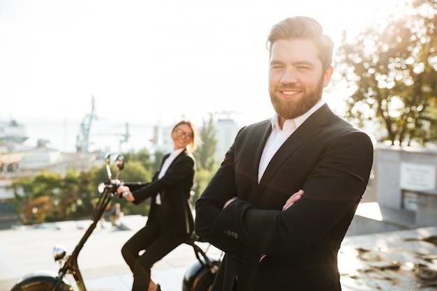 幸せなビジネスの男性が組んだ腕を持って屋外でポーズ
