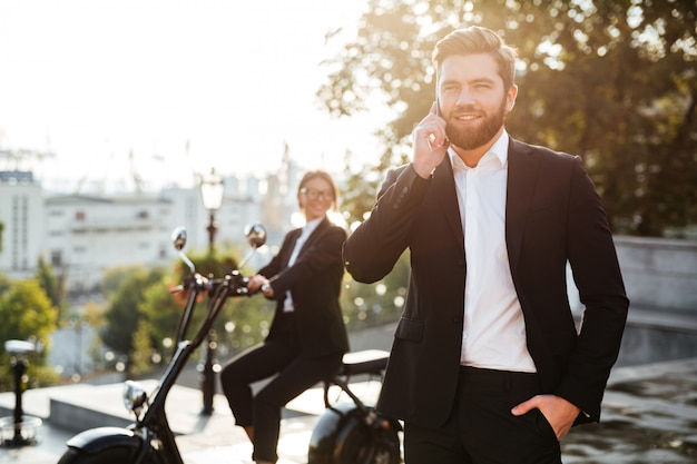 Happy business man posing outdoors talking by phone